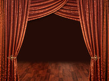 Theatre curtains, copper red. Red theater stage curtains brown wooden floor and dark background royalty free stock photos