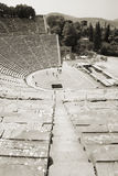 Theatre of Epidaurus, Greece. Black and White view of an ancient circular amphitheater in Epidaurus, Peloponnese - Greece Royalty Free Stock Photo