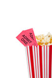 Theatre popcorn container with movie ticket. Theatre popcorn container with two movie tickets on a white background with copy space Royalty Free Stock Image