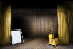 Theatre Stage. A stage with wooden floor and wooden paneled backdrop.  Yellow curtains and a blank sign with copy space.  Cleaning bucket is concept for cleaning Stock Photo
