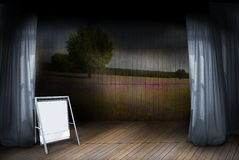 Theatre Stage. A stage with wooden floor and wooden paneled backdrop with pasture.  Blue worn curtains and a blank sign with copy space.  Concept for announcing Stock Image