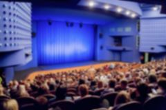 Theatre stage. Blue curtain. Defocused image, bokeh effect. People in the auditorium of the theater or concert hall royalty free stock images
