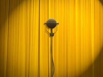 Theatre stage with closed curtains and microphone. Stage of the theatre with yellow curtains closed and old fashion microphone in front of the curtains Royalty Free Stock Photo