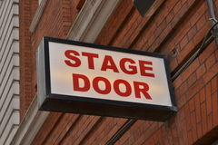 Theatre stage door sign. With red brick wall in the background Royalty Free Stock Images