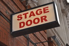 Theatre stage door sign. With red brick wall and buildings columns in the background Royalty Free Stock Photography