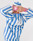 Theatrical criminal. Theatrical performer dressed in prison costume with hands behind head, rear view on white background Stock Photos