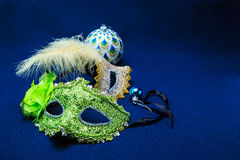 Theatrical masks with ornaments, a feather and a sphere. Theatrical masks with ornaments against a dark background Stock Photo