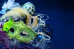 Theatrical masks with ornaments, a tinsel and a beads. Theatrical masks with ornaments, a tinsel against a dark background Stock Images