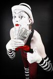 Theatrical mime with dollars in their hands Stock Images
