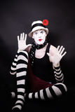 Theatrical mime with red flower sits on the floor Royalty Free Stock Photography