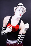 Theatrical mime in white hat and striped gloves Stock Images