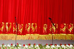Theatrical red velvet curtain with gold pattern, and the microphones royalty free stock photo