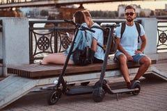 Thee老friengs坐长凳在河沿 免版税库存照片