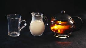 Thee in een glastheepot, de thee in een transparante Kop en een kleine kruik melk stock video