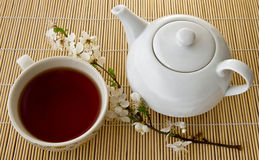 Thee in een kop en theepot, verse bloemen op een achtergrond van bamboeraad Royalty-vrije Stock Afbeelding