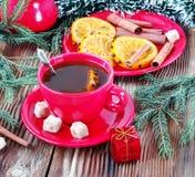 Thee in een rode mok met kaneel en sinaasappelen Stock Foto