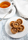 Thee en taartjes met boterroom en okkernoten Stock Afbeelding