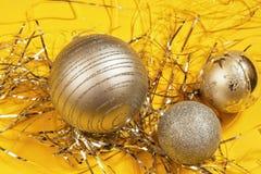 Thee jul klumpa ihop sig på gul bakgrund med den metalliska tråden Arkivbild