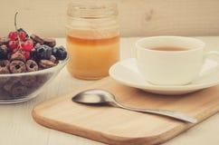 Thee, lepel, honing en vlokken met bessen/thee, lepel, honing en vlokken met bessen op een houten dienblad Selectieve fokus stock fotografie