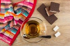 Thee, lepel, suiker, gebroken wafeltje in chocolade en servet royalty-vrije stock foto's