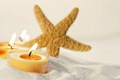 Thee lichte kaarsen in zand met stervissen Stock Foto's