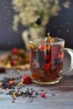 Thee met bessen en bloemblaadjes in glas worden gegoten dat Royalty-vrije Stock Afbeeldingen