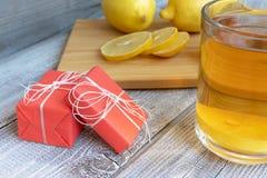 Thee met citroen op een houten lijst, vakantie huidige vakjes en stukken van gedobbelde citroen stock afbeelding