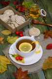Thee met citroen op een lijst met de herfstgebladerte dat wordt uitgestrooid Royalty-vrije Stock Afbeelding