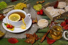 Thee met citroen op een lijst met de herfstgebladerte dat wordt uitgestrooid Stock Foto's