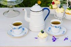 Thee met cupcakes in een uitstekende theepot Stock Afbeelding