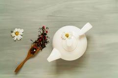 Thee met kruiden in een witte ceramische theepot op een lichte houten achtergrond, concept een theeceremonie, hoogste mening Royalty-vrije Stock Afbeeldingen
