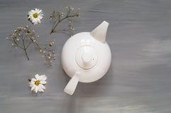 Thee met kruiden in een witte ceramische theepot op een lichte houten achtergrond, concept een theeceremonie, hoogste mening Stock Afbeelding
