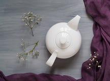 Thee met kruiden in een witte ceramische theepot op een lichte houten achtergrond met een ultraviolette sjaal, hoogste mening Royalty-vrije Stock Fotografie
