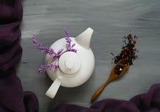 Thee met kruiden en rode harten in een witte ceramische theepot op een lichte houten achtergrond met een ultraviolette sjaal, hoo Stock Fotografie
