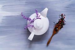 Thee met kruiden van ultraviolette kleur in een witte ceramische theepot op een lichte houten achtergrond, concept een theeceremo Stock Foto