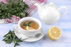 Thee met munt en citroen, ketel op blauwe houten hoogste mening als achtergrond stock foto