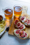 Thee met snaks met fig. en roomkaas op witte textielachtergrond Stock Afbeeldingen