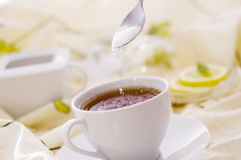 Thee met witte kop met suiker Stock Foto