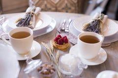 Thee met witte koppen en cakes Stock Foto