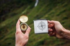 Thee op een mok van het toeristenmetaal en een kompas in Hand Natuurlijke achtergrond Uitstekende toon royalty-vrije stock foto
