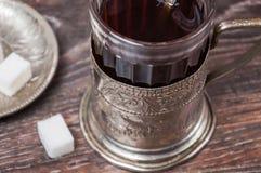 Thee in uitstekend glas met glas-houder Stock Foto's