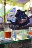 Thee van een theepot in een glasmok die wordt gegoten royalty-vrije stock afbeelding