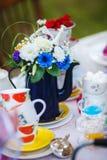 Theeketel die met bloemen wordt verfraaid Koppen op de platen Royalty-vrije Stock Foto