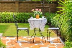Theekop en bloem in vaas op de lijst met een stoel in Th Stock Afbeelding