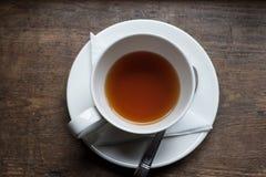 Theekop en thee van bovenkant op houten lijst Stock Afbeelding