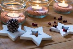 Theelichten in kruiken met zoute, houten sterren, denneappel en rode bessenkerstmis, Nieuwjaar, komst Royalty-vrije Stock Afbeeldingen