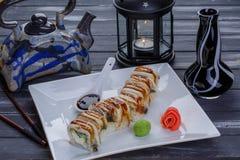 Theepot en de sushi met palingsvissen, nigiri, maguro en sushibroodjes wordt de geplaatst dienden op witte plaat op donkere houte royalty-vrije stock afbeeldingen