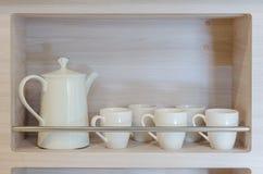 Theepot en koppen op houten plank stock afbeeldingen