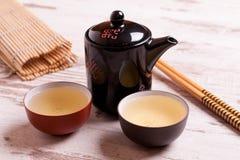 Theepot en koppen van groene thee op een witte houten achtergrond Stock Foto