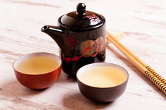 Theepot en koppen van groene thee op een witte houten achtergrond Royalty-vrije Stock Foto